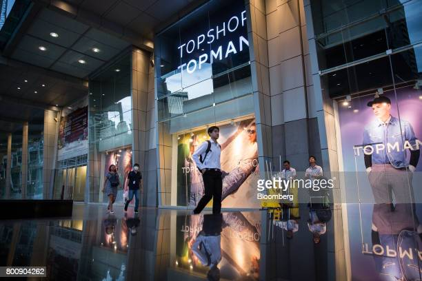 Pedestrians walk past advertising in the windows of a Topshop store operated by Arcadia Group Ltd outside the CentralWorld shopping mall in Bangkok...