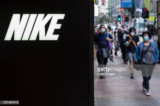 Pedestrians walk past American multinational sport clothing brand, Nike store and its logo seen in Hong Kong.