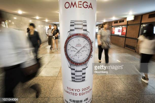 Pedestrians walk past an advertisement for an Omega Speedmaster wristwatch produced by Omega SA a unit of Swatch Group AG in the Ginza area of Tokyo...