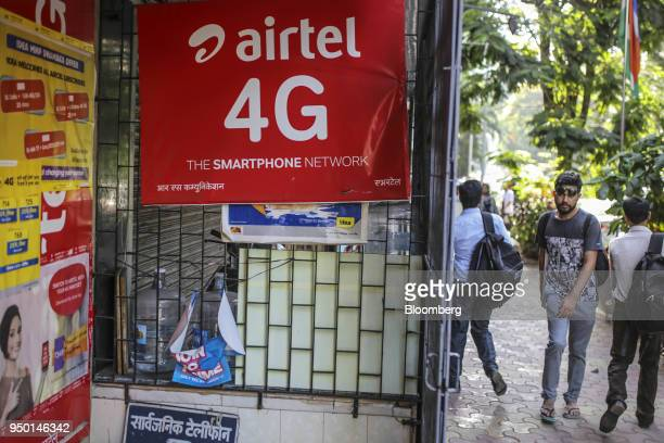 Pedestrians walk past an advertisement for Bharti Airtel Ltd outside a sim card store in Mumbai India on Saturday April 21 2018 Bharti Airtel are...