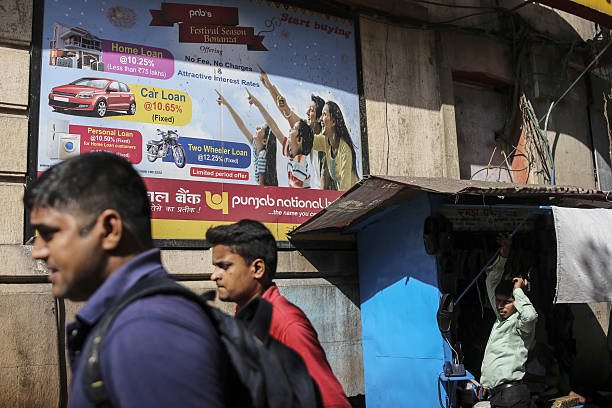 Pedestrians walk past an advertisement for Punjab National Bank in Mumbai India on Friday Jan 27 2017 India`s Finance Ministry will recommend bold...