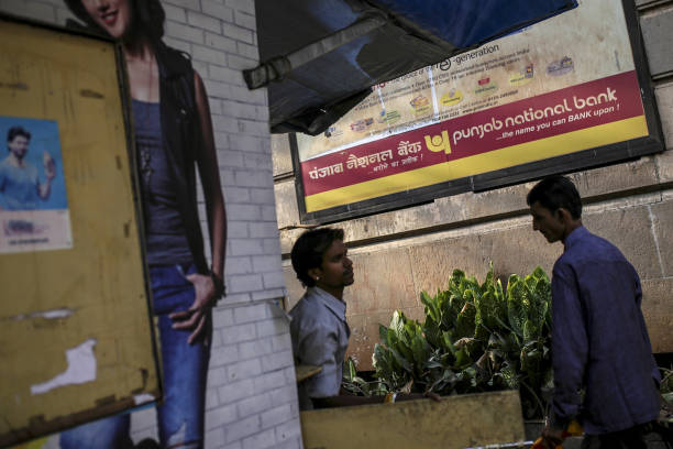 Pedestrians walk past an advertisement for Punjab National Bank in Mumbai India on Wednesday Feb 14 2018 PNB one of India`s biggest banks has accused.