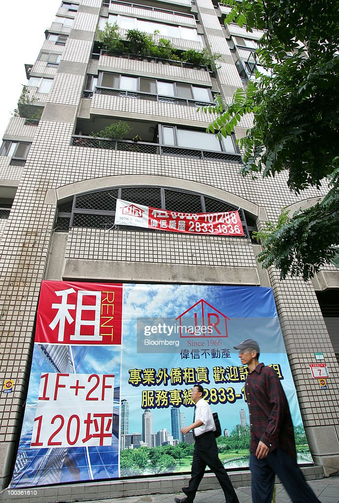 Pedestrians walk past an advertisement for renting houses in Taipei, Taiwan, on Saturday, May 22, 2010. Investors should sell Taipei property now, taking advantage of a 21-month rally in prices before the government acts to make real estate more affordable, according to the Taiwan Real Estate Research Center and the island's largest real-estate brokerage. Photographer: Maurice Tsai/Bloomberg via Getty Images