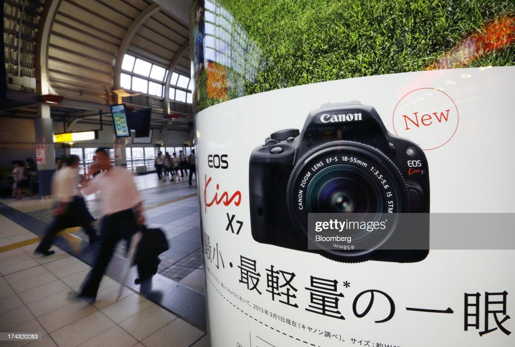Pedestrians walk past an advertisement for the Canon Inc. EOS Kiss X7 digital single-lens reflex (DSLR) camera in Tokyo, Japan, on Tuesday, July 23, 2013. Canon Inc., the world's largest camera maker, is scheduled to release earnings on July 24. Photographer: Tomohiro Ohsumi/Bloomberg via Getty Images