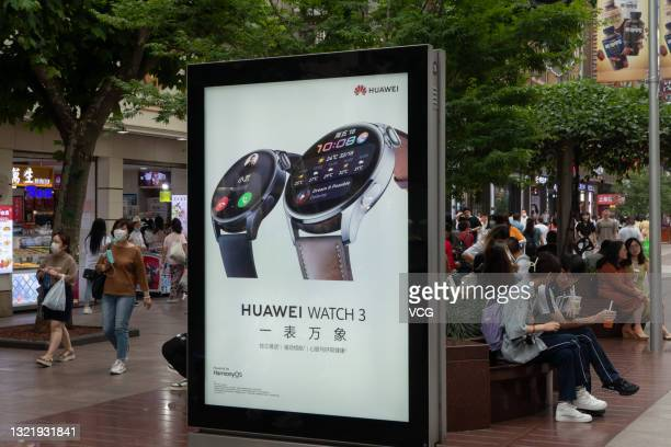 Pedestrians walk past an advertisement for the Huawei Watch 3 at Nanjing Road Pedestrian Street on June 4, 2021 in Shanghai, China.