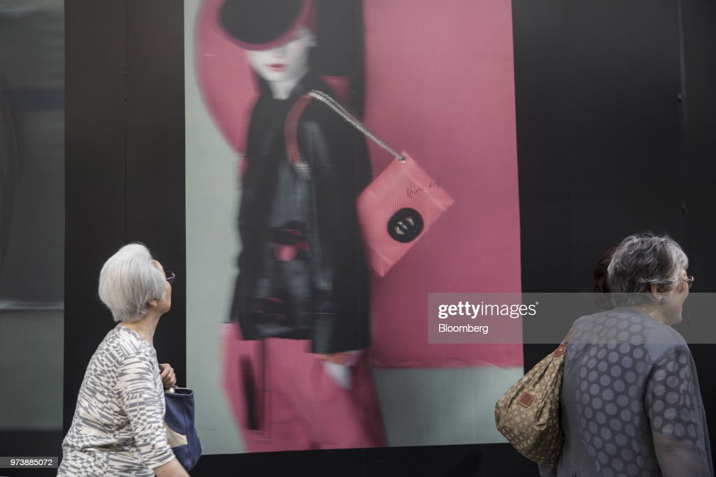 Pedestrians walk past an advertisement in the Ginza district of Tokyo, Japan, on Friday, May 25, 2018. The savings-rich elderly spend about 9.7 trillion yen ($87 billion) a year on their offspring and such spending last year accounted for about a third of the modest growth in total consumption, according toHiromichi Shirakawa, chief Japan economist at Credit Suisse Group. Photographer: Shiho Fukada/Bloomberg via Getty Images