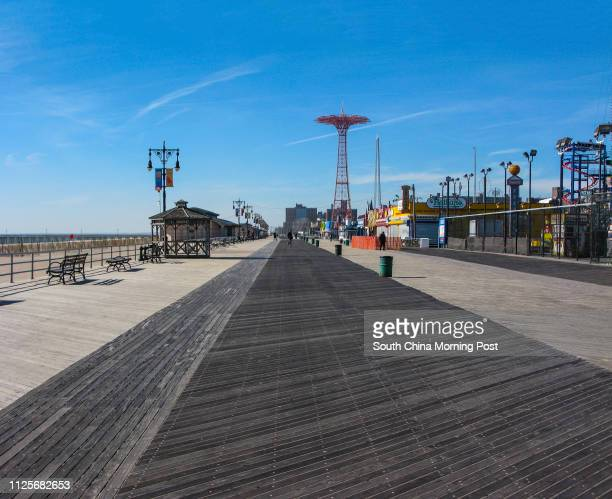 Pedestrians walk past an almost deserted board walk on Coney Island in New York on 15 November 2013 [05JANUARY2014 TRAVEL POST MAGAZINE]