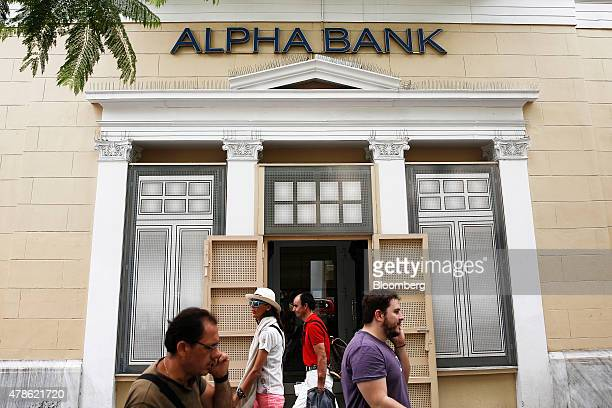 Pedestrians walk past an Alpha Bank AE bank branch in Athens Greece on Friday June 26 2015 Greek Prime Minister Alexis Tsipras says he will defend...