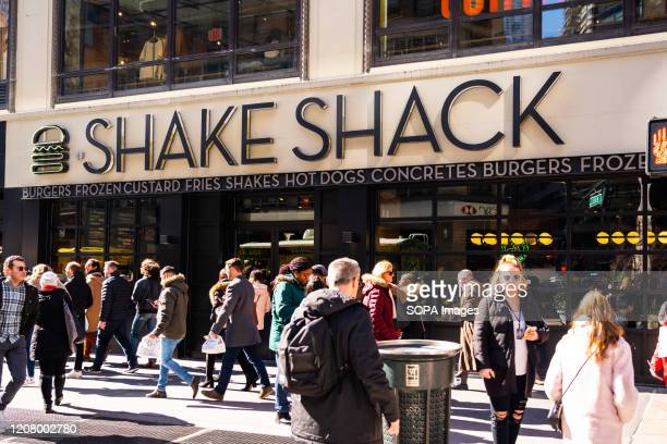 Pedestrians walk past an American fast casual restaurant chain, Shake Shack store in New York City.