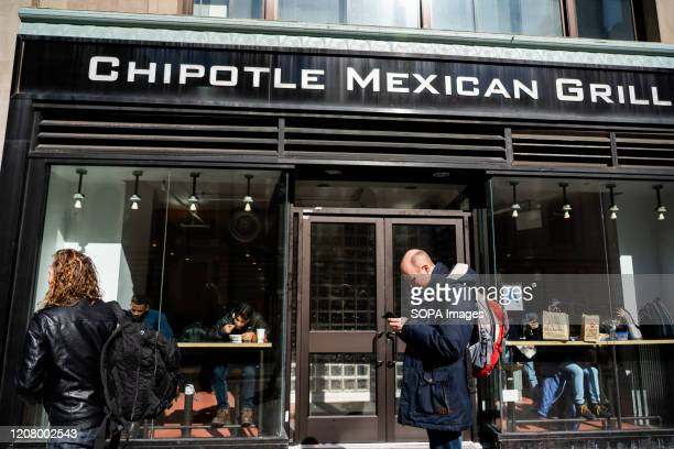Pedestrians walk past an American fast casual restaurants chain Chipotle Mexican Grill store in Midtown Manhattan