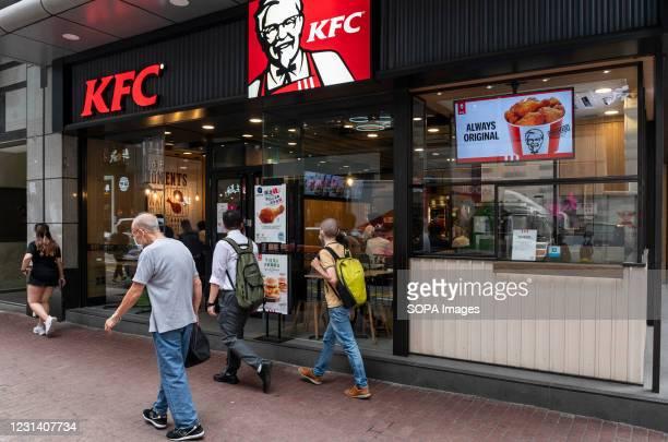 Pedestrians walk past an American fast food chicken restaurant chain, Kentucky Fried Chicken and logo seen in Hong Kong.