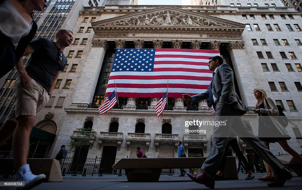 Pedestrians walk past an American flag displayed outside of the New York Stock Exchange (NYSE) in New York, U.S., on Monday, Sept. 12, 2016. U.S. stocks rebounded after the biggest rout since June wiped about $500 billion from the value of equities, while Treasury yields held near two-month highs before the Federal Reserve's Lael Brainard official speaks. Emerging-market assets slumped. Photographer: Michael Nagle/Bloomberg via Getty Images