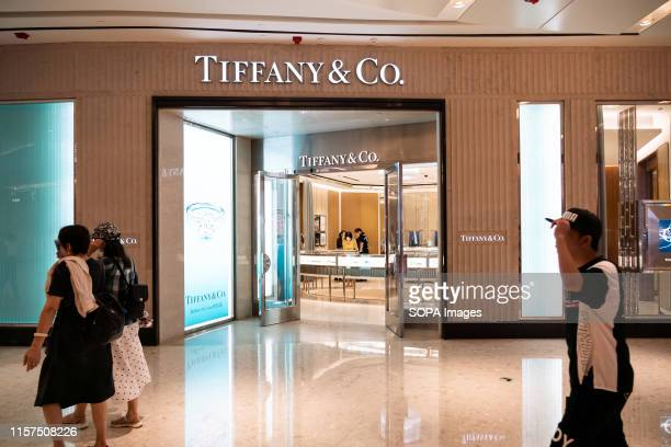 Pedestrians walk past an American luxury jewellery and speciality retailer Tiffany Co store in Shanghai