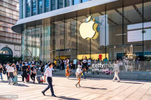 Pedestrians walk past an American multinational technology company Apple retail store on East Nanjing Road in Shanghai. Apple launched sales of its...