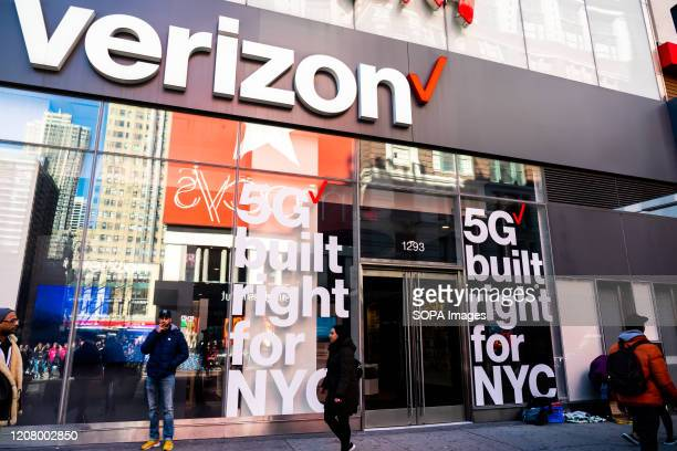Pedestrians walk past an American multinational telecommunications conglomerate Verizon store in New York City
