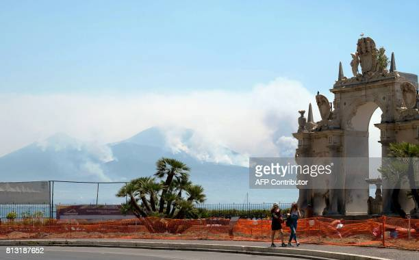 Pedestrians walk past an ancient gateway as smoke rises from fires on the slopes of the volcano of Mount Vesuvius east of Naples on July 12 2017...