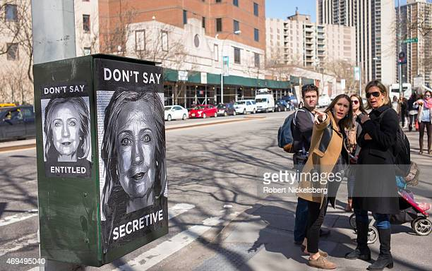 Pedestrians walk past an antiHillary Clinton poster across the street from the purported Clinton campaign headquarters on April 12 2015 in the...