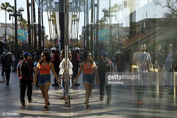 Pedestrians walk past an Apple Inc store at the Third Street Promenade in Santa Monica California US on Tuesday March 22 2016 The Bloomberg Consumer...