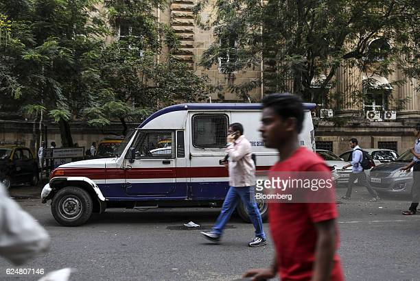 Pedestrians walk past an armoured van near a State Bank of India branch in Mumbai India on Friday Nov 18 2016 India's top court refused to stay...