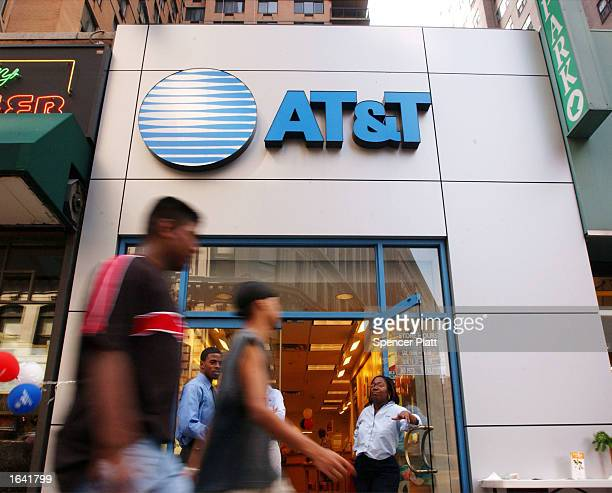 Pedestrians walk past an ATT Wireless store July 9 2001 in New York City Federal regulators approved the merger of Comcast and ATT Broadband November...
