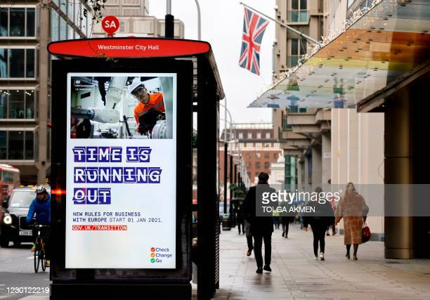 Pedestrians walk past an BTier 2 Coronavirus information displayed on an electronic advertising board at a bus stop in central London on December 14,...
