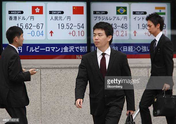Pedestrians walk past an electronic board displaying exchange rate of the yen against the Hong Kong dollar left and the Chinese yuan second from left...
