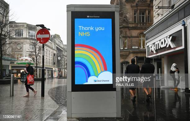 Pedestrians walk past an electronic display board thanking the workers of Britain's NHS in Liverpool, on January 13 as non-essential retailers keep...