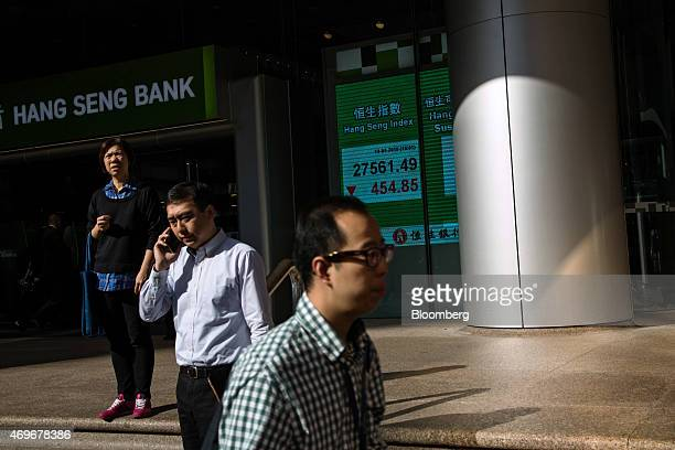 Pedestrians walk past an electronic display showing the closing figure of the Hang Seng Index at the Hang Seng Bank Ltd headquarters in Hong Kong...