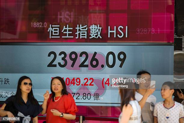Pedestrians walk past an electronic display showing the Hang Seng Index figure in Hong Kong China on Wednesday July 8 2015 Hong Kong's benchmark...