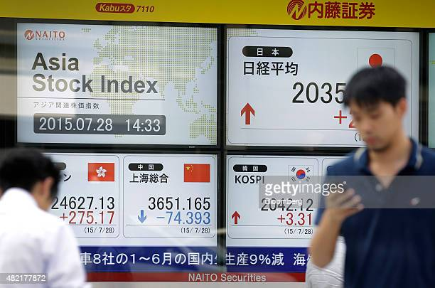 Pedestrians walk past an electronic stock board displaying the figure of the Nikkei 225 Stock Average top right the Hang Seng Index bottom left the...