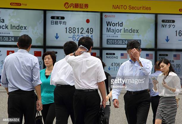 Pedestrians walk past an electronic stock board displaying the Nikkei 225 Stock Average outside a securities firm in Tokyo Japan on Monday Aug 24...