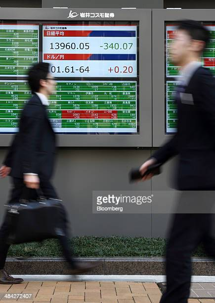 Pedestrians walk past an electronic stock board displaying the closing figure of the Nikkei 225 Stock Average center top and the exchange rate of the...