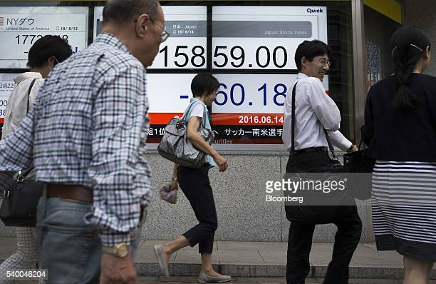 Pedestrians walk past an electronic stock board displaying the closing figure of the Nikkei Stock Average outside a securities firm in Japanese...