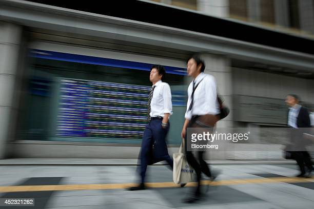 Pedestrians walk past an electronic stock board outside a securities firm in Tokyo Japan on Friday July 18 2014 Japanese stocks fell with the Topix...