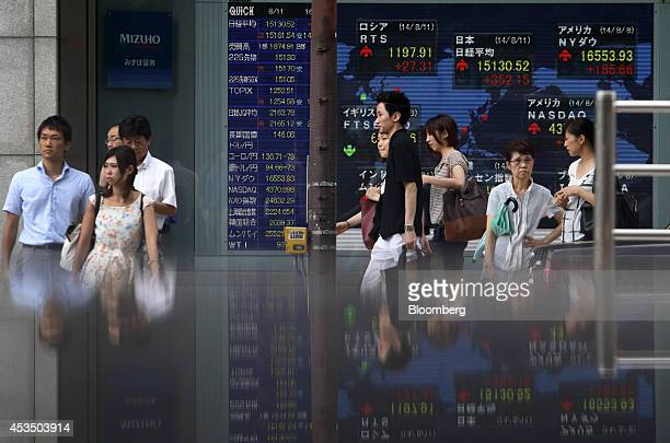 Pedestrians walk past an electronic stock board outside a securities firm in Tokyo Japan on Monday Aug 11 2014 Japans Topix index rebounded from its...