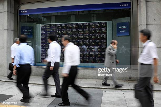 Pedestrians walk past an electronic stock board outside a securities firm in Tokyo Japan on Wednesday Sept 3 2014 Japan's Topix index rose on heavy...