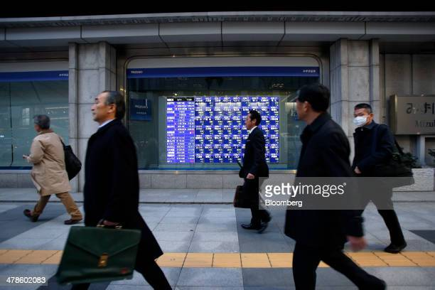 Pedestrians walk past an electronic stock board outside a securities firm in Tokyo Japan on Friday March 14 2014 Japanese shares fell with the Topix...