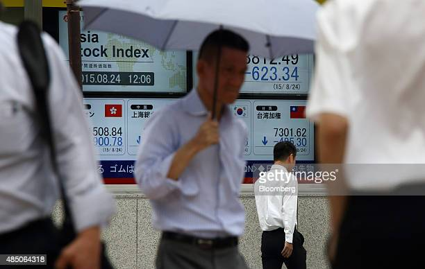 Pedestrians walk past an electronic stock board outside a securities firm in Tokyo Japan on Monday Aug 24 2015 Japanese stocks plunged the most since...