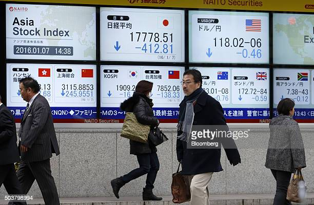 Pedestrians walk past an electronic stock board outside a securities firm in Tokyo Japan on Thursday Jan 7 2016 Japanese stocks fell for a fourth day...