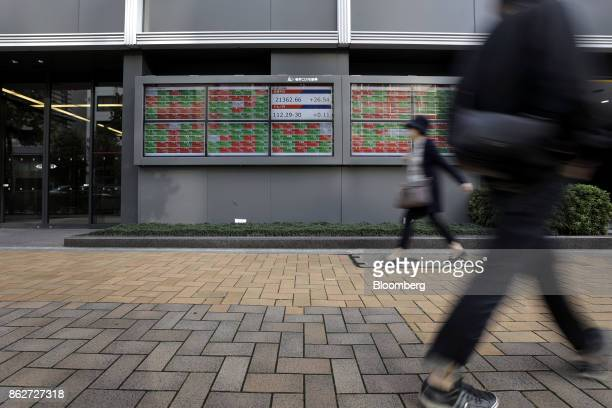 Pedestrians walk past an electronic stock board outside a securities firm in Tokyo Japan on Wednesday Oct 18 2017 As Prime Minister Shinzo Abe's...