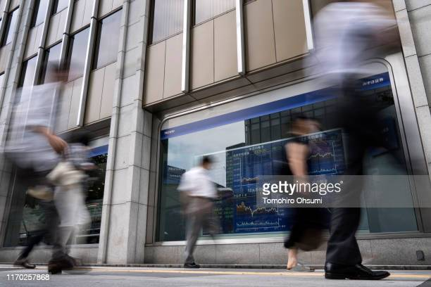 Pedestrians walk past an electronic stock board outside a security firm on August 26, 2019 in Tokyo, Japan. Japanese stocks dropped and the yen...