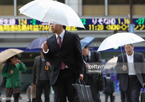 Pedestrians walk past an electronic stock ticker outside a securities firm in Tokyo, Japan, on Wednesday, April 28, 2010. Japanese stocks fell as a...