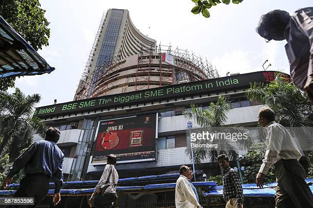 Pedestrians walk past an electronic ticker board at the Bombay Stock Exchange in Mumbai India on Tuesday Aug 9 2016 Presiding over his final...