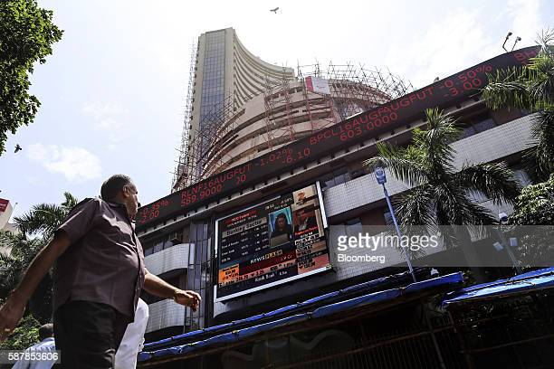 Pedestrians walk past an electronic ticker board displaying stock figures at the Bombay Stock Exchange in Mumbai India on Tuesday Aug 9 2016...
