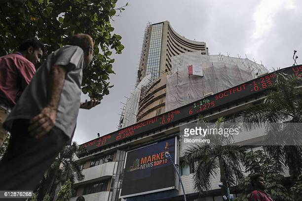 Pedestrians walk past an electronic ticker board displaying stock figures at the Bombay Stock Exchange which stands partially covered by scaffolding...