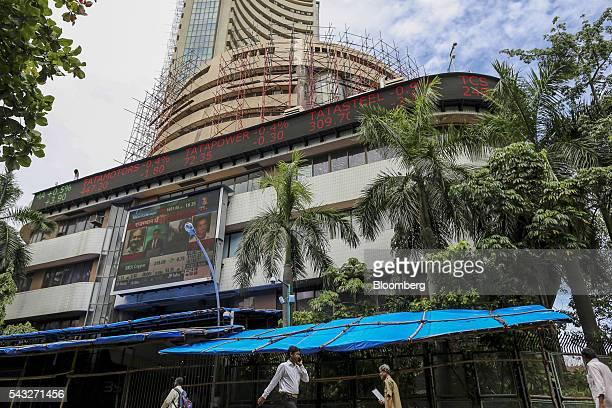 Pedestrians walk past an electronic ticker board displaying stock figures for Tata Motors Ltd left to right Tata Power Co Tata Steel Ltd and Tata...