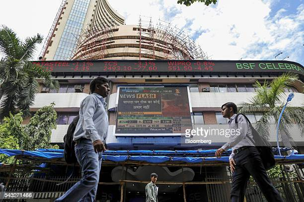 Pedestrians walk past an electronic ticker board displaying stock figures for Tata Steel Ltd from left Tata Consultancy Services Ltd and Wipro Ltd at...
