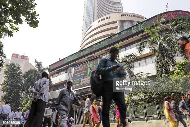 Pedestrians walk past an electronic ticker board that indicates stock figures at the Bombay Stock Exchange in Mumbai India on Friday Jan 8 2016...