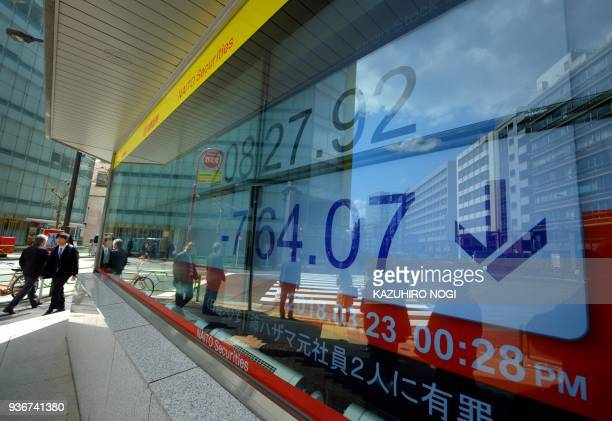 Pedestrians walk past an electronics stock indicator showing share prices on the Tokyo Stock Exchange in Tokyo on March 23 2018 Tokyo stocks plunged...