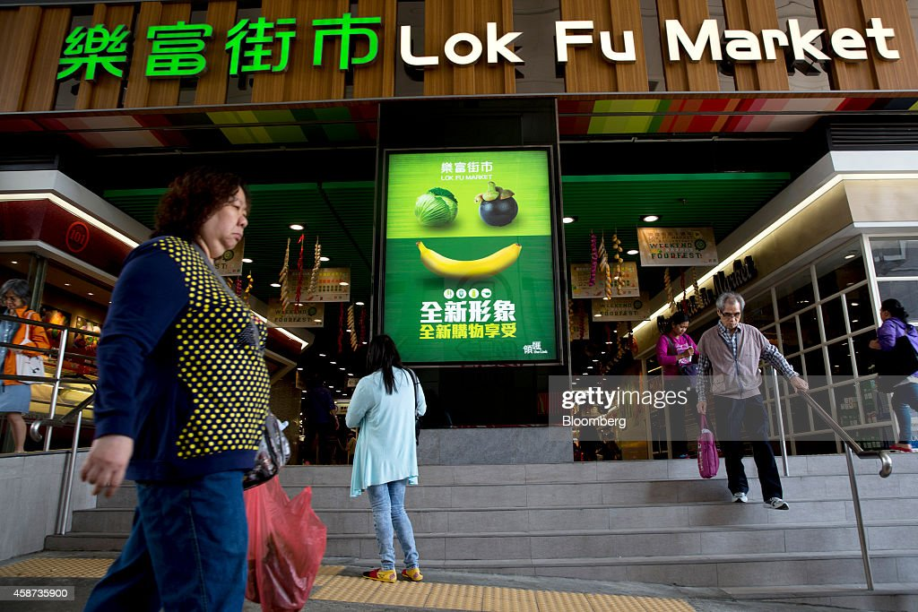 Pedestrians walk past an entrance of Lok Fu Market, operated by the Link Real Estate Investment Trust (REIT), in Hong Kong, China, on Monday, Nov. 10, 2014. The Link REIT, Asia's largest property trust which owns neighborhood malls, food markets, and car parks, is scheduled to announce interim results on Nov. 13. Photographer: Brent Lewin/Bloomberg via Getty Images